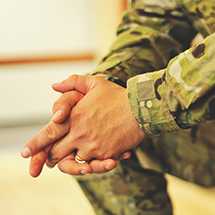Hands of person in uniform clasped together