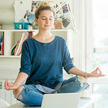 Student meditating in front of laptop